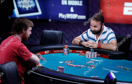 Daniel Negreanu, right, looks at Joseph McKeehen as they play at the World Series of Poker main event, in Las Vegas