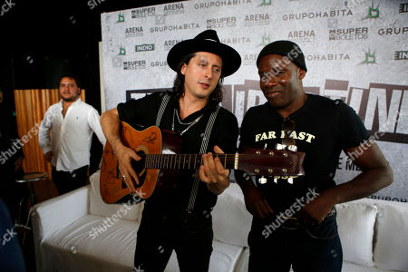 Guitarist Carl Barat, of the English rock band The Libertines, strums a guitar handed to him to sign as he stands with drummer Gary Powell following a press conference in Mexico City. The Libertines will perform at Mexico City Arena on Oct. 5