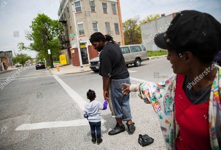 Monica Bailey, Terrance McCourt, Ariel Rose Area resident Monica Bailey, right, talks with Terrance McCourt as he crosses a street with niece Ariel Rose, 2, in Baltimore, across the street from a corner convenience store where privately owned camera footage revealed a new stop a police van made while transporting Freddie Gray. Deputy Commissioner Kevin Davis said the stop was previously unknown to investigators. It was one of four stops the vehicle made after Gray was put inside. Gray suffered a critical spinal injury at some point during his arrest and died a week later