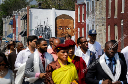 Stock Photo of Gyalwang Drukpa A mural depicting Freddie Gray is seen on the side of a row house above the Gyalwang Drukpa, bottom center, the Buddhist leader of South Asia, as he takes a walking tour alongside other faith and community leaders, in Baltimore. The group visited the site of Gray's arrest and a store that was damaged by fire during last month's unrest