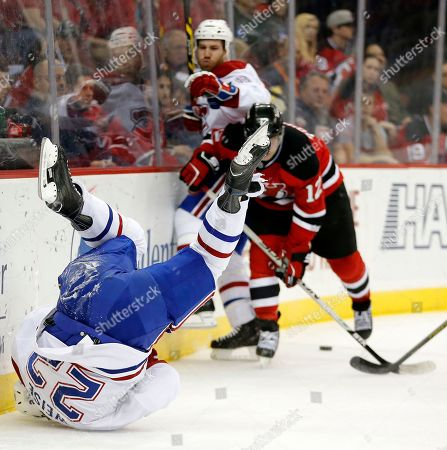 Reid Boucher, Dale Weise, Brandon Prust Montreal Canadiens right wing Dale Weise, left, rolls on his shoulder after hitting the boards as New Jersey Devils center Reid Boucher (12) battles for the puck with Brandon Prust, back, during the first period of an NHL hockey game, in Newark, N.J