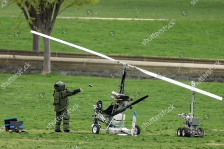 A member of a bomb squad pulls something off of a small helicopter and throws it after a man landed on the West Lawn of the Capitol in Washington, . Police arrested a man who steered his tiny, one-person helicopter onto the West Lawn of the U.S. Capitol Wednesday, astonishing spring tourists and prompting a temporary lockdown of the Capitol Visitor Center. Capitol Police didn't immediately identify the pilot or comment on his motive, but a Florida postal carrier named Doug Hughes took responsibility for the stunt on a website where he said he was delivering letters to all 535 members of Congress in order to draw attention to campaign finance corruption