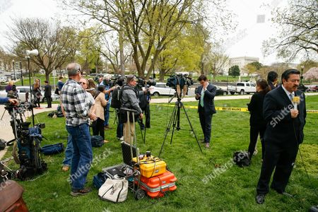 Members of the media converge near Constitution Avenue on Capitol Hill in Washington, after a small helicopter landed on the West Lawn of the Capitol. Police arrested a man who steered his tiny, one-person helicopter onto the West Lawn of the U.S. Capitol Wednesday, astonishing spring tourists and prompting a temporary lockdown of the Capitol Visitor Center. Capitol Police didn't immediately identify the pilot or comment on his motive, but a Florida postal carrier named Doug Hughes took responsibility for the stunt on a website where he said he was delivering letters to all 535 members of Congress in order to draw attention to campaign finance corruption