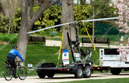 A Capitol Police officer on bike, follows a small helicopter loaded on a Capitol Police trailer, after a man landed on the West Lawn of the Capitol in Washington, . Police arrested a man who steered his tiny, one-person helicopter onto the West Lawn of the U.S. Capitol Wednesday, astonishing spring tourists and prompting a temporary lockdown of the Capitol Visitor Center. Capitol Police didn't immediately identify the pilot or comment on his motive, but a Florida postal carrier named Doug Hughes took responsibility for the stunt on a website where he said he was delivering letters to all 535 members of Congress in order to draw attention to campaign finance corruption
