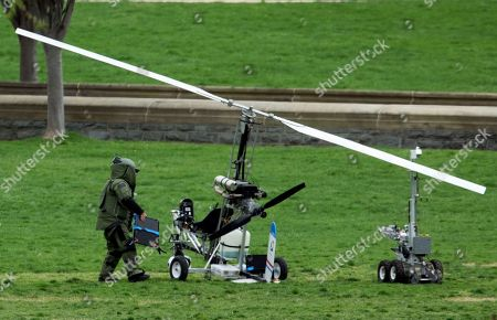 A member of a bomb squad checks a small helicopter after a man landed on the West Lawn of the Capitol in Washington, . Police arrested a man who steered his tiny, one-person helicopter onto the West Lawn of the U.S. Capitol Wednesday, astonishing spring tourists and prompting a temporary lockdown of the Capitol Visitor Center. Capitol Police didn't immediately identify the pilot or comment on his motive, but a Florida postal carrier named Doug Hughes took responsibility for the stunt on a website where he said he was delivering letters to all 535 members of Congress in order to draw attention to campaign finance corruption