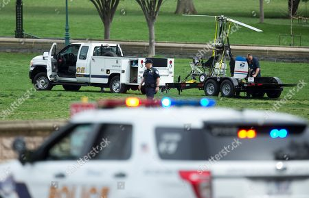 A small helicopter is loaded onto a trailer, after a man landed on the West Lawn of the Capitol in Washington, . Police arrested a man who steered his tiny, one-person helicopter onto the West Lawn of the U.S. Capitol Wednesday, astonishing spring tourists and prompting a temporary lockdown of the Capitol Visitor Center. Capitol Police didn't immediately identify the pilot or comment on his motive, but a Florida postal carrier named Doug Hughes took responsibility for the stunt on a website where he said he was delivering letters to all 535 members of Congress in order to draw attention to campaign finance corruption