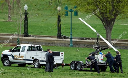 Capitol Police officers load a small helicopter onto a trailer, after a man landed on the West Lawn of the Capitol in Washington, . Police arrested a man who steered his tiny, one-person helicopter onto the West Lawn of the U.S. Capitol Wednesday, astonishing spring tourists and prompting a temporary lockdown of the Capitol Visitor Center. Capitol Police didn't immediately identify the pilot or comment on his motive, but a Florida postal carrier named Doug Hughes took responsibility for the stunt on a website where he said he was delivering letters to all 535 members of Congress in order to draw attention to campaign finance corruption