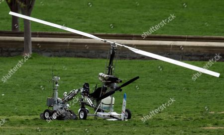 A robot checks a small helicopter a man landed on the West Lawn of the Capitol in Washington, . Police arrested a man who steered his tiny, one-person helicopter onto the West Lawn of the U.S. Capitol Wednesday, astonishing spring tourists and prompting a temporary lockdown of the Capitol Visitor Center. Capitol Police didn't immediately identify the pilot or comment on his motive, but a Florida postal carrier named Doug Hughes took responsibility for the stunt on a website where he said he was delivering letters to all 535 members of Congress in order to draw attention to campaign finance corruption