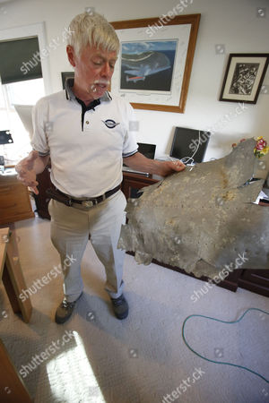 Ric Gillespie, who heads The International Group for Historic Aircraft Recovery, holds a piece of metal at his home office in Oxford, Pa., . The artifact is one of the more controversial finds from TIGHAR expeditions to the island of Nikumaroro in the South Pacific. The group has spent years in search of any sign of Amelia Earhart and her navigator, Fred Noonan, on the island. After the metal was found in the early 1990s, Gillespie claimed it was from Earhart's Lockheed Electra from her attempt at an around-the-world flight. Experts have varying opinions about whether the metal could be from the plane