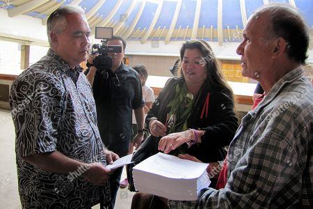 Mike McCartney Mike McCartney, left, Gov. David Ige's chief of staff, accepts a stack of papers containing comments against building a giant telescope near the summit of Mauna Kea. Members of a group opposing the project delivered the papers and a thumb drive containing petition signatures to the governor's office at the Hawaii Capitol in Honolulu on