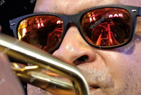 Stock Image of Irvin Mayfield The hands and trumpet of jazz recording artist Irvin Mayfield are reflected in his glasses as he performs at the New Orleans Jazz and Heritage Festival in New Orleans