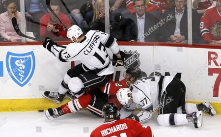 Kyle Clifford, Nick Shore, Duncan Keith Chicago Blackhawks defenseman Duncan Keith (2) is sandwiched between Los Angeles Kings left wing Kyle Clifford (13) and Nick Shore (37) during the third period of an NHL hockey game, in Chicago. The Blackhawks won 4-1