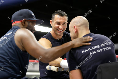 Wladimir Klitschko, Aldo Vetere, Johnathon Banks Heavyweight World Champion boxer Wladimir Klitschko, center, smiles as he talks with head trainer Johnathon Banks, left, as his hands are tapped by physical therapist and athletic coach Aldo Vetere during a media workout at the Lucky Street Gym, in Hollywood, Fla. Klitschko will defend his WBA and IBF heavyweight titles against Bryant Jennings on April 25 at Madison Square Garden