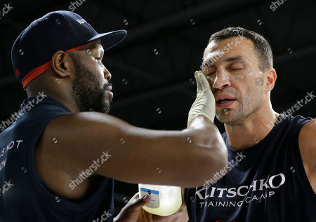 Wladimir Klitschko, Johnathon Banks Head trainer Johnathon Banks, left, applies petroleum jelly on the face of Heavyweight World Champion boxer Wladimir Klitschko during a media workout at the Lucky Street Gym, in Hollywood, Fla. Klitschko will defend his WBA and IBF heavyweight titles against Bryant Jennings on April 25 at Madison Square Garden