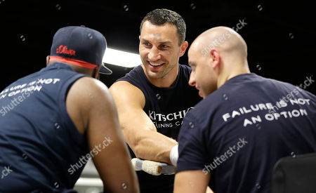 Wladimir Klitschko, Aldo Vetere, Johnathon Banks Heavyweight World Champion boxer Wladimir Klitschko, center, talks with head trainer Johnathon Banks, left, as his hands are tapped by physical therapist and athletic coach Aldo Vetere during a media workout at the Lucky Street Gym, in Hollywood, Fla. Klitschko will defend his WBA and IBF heavyweight titles against Bryant Jennings on April 25 at Madison Square Garden