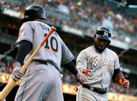 Jeff Baker, Marcell Ozuna Miami Marlins' Marcell Ozuna, right, is congratulated by teammate Jeff Baker (10) after hitting a home run off San Francisco Giants' Madison Bumgarner in the fourth inning of a baseball game, in San Francisco