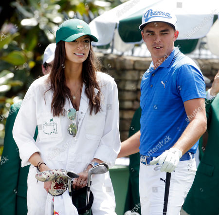 Stock Picture of Rickie Fowler with his caddie Alexis Randock during the Par 3 contest at the Masters golf tournament, in Augusta, Ga
