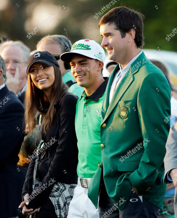 Stock Photo of Rickie Fowler stands with his friend Alexis Randock and defending Masters' champion Bubba Watson, right, before the honorary first tee during the first round of the Masters golf tournament, in Augusta, Ga