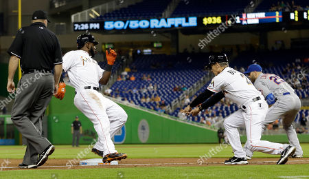 Stock Photo of Marcell Ozuna, Brett Butler Miami Marlins' Marcell Ozuna, left, is safe at third base on a fly-ball by Michael Morse in the first inning of a baseball game against the New York Mets, as third base coach Brett Butler (2) gives Ozuna a sign, in Miami