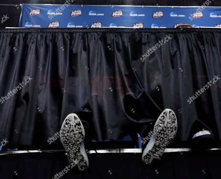 Wisconsin's Sam Dekker sits with his legs stretched out during a news conference for the NCAA Final Four college basketball tournament championship game, in Indianapolis