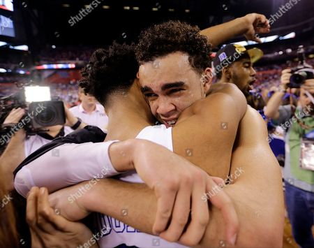 Duke's Tyus Jones, right, hugs Quinn Cook after the NCAA Final Four college basketball tournament championship game against Wisconsin, in Indianapolis. Duke won 68-63