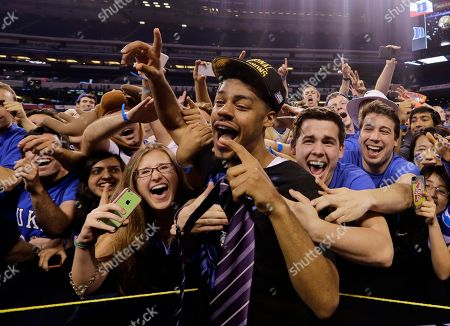 Duke's Quinn Cook celebrates their 68-63 victory over Wisconsin with fans in the NCAA Final Four college basketball tournament championship game, in Indianapolis