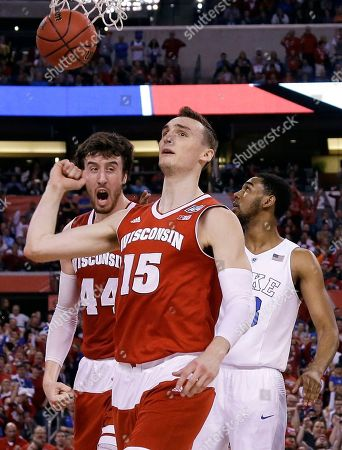 Wisconsin's Sam Dekker (15) and teammate Frank Kaminsky, left, celebrate in front of Duke's Matt Jones, right, during the first half of the NCAA Final Four college basketball tournament championship game, in Indianapolis
