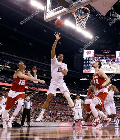 Duke's Jahlil Okafor, center, shoots between Wisconsin defenders Sam Dekker, left, and Frank Kaminsky, right, during the second half of the NCAA Final Four college basketball tournament championship game, in Indianapolis