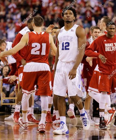 Duke's Justise Winslow (12) walks to the bench during a timeout as Wisconsin players celebrate a three-point basket during the second half of the NCAA Final Four college basketball tournament championship game, in Indianapolis