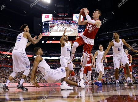 Wisconsin's Sam Dekker (15) shoots over Kentucky's Willie Cauley-Stein, from left, Aaron Harrison, Karl-Anthony Towns and Andrew Harrison, right, during the first half of the NCAA Final Four tournament college basketball semifinal game, in Indianapolis