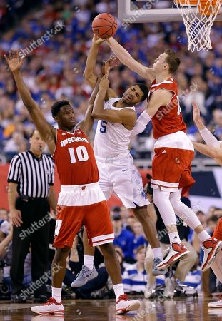 Kentucky's Andrew Harrison, center, fights for a rebound with Wisconsin's Nigel Hayes, left, and Sam Dekker, right, during the second half of the NCAA Final Four tournament college basketball semifinal game, in Indianapolis