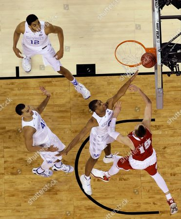 Kentucky's Aaron Harrison tries to block a shot by Wisconsin's Sam Dekker (15) during the second half of the NCAA Final Four tournament college basketball semifinal game, in Indianapolis