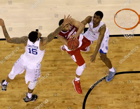 Wisconsin's Traevon Jackson goes up for a shot against Kentucky's Willie Cauley-Stein (15) and Andrew Harrison (5) during the second half of the NCAA Final Four tournament college basketball semifinal game, in Indianapolis