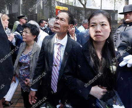 Wenjian Liu Pei Xia Chen, right, widow of slain New York City Police Detective Wenjian Liu, stands with his parents Xiu Yan Li, left, and Wei Tang Liu after a ceremony at the New York State Police Officers Memorial, in Albany, N.Y. They waited as a worker traced Liu's name on paper from the memorial. Eight officers who died last year from line-of-duty injuries have been honored at the memorial, along with 14 who died from illnesses related to recovery work at the World Trade Center destroyed by terrorists in 2001