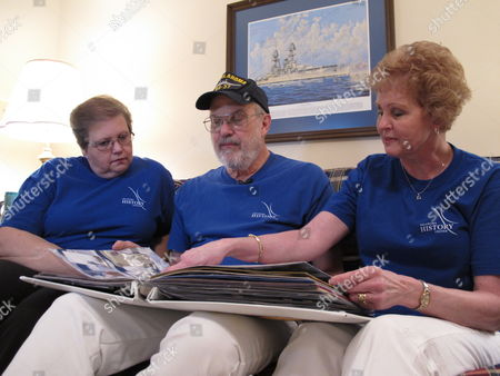 Siblings, from left, Colleen Williams, Brad McDonald and Dawn Silsbee look through a scrapbook in Cary, N.C. on . They have submitted DNA samples in hopes of identifying their uncle, Bert Jacobson, who died on the USS Oklahoma during the Dec. 7, 1941, attack at Pearl Harbor