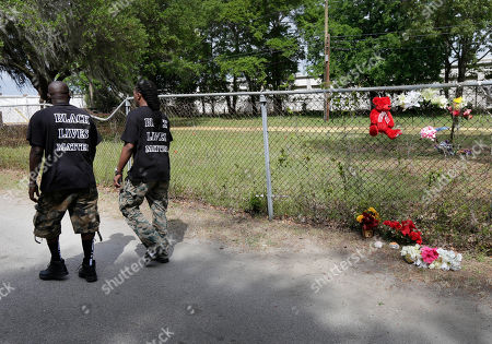 Stock Image of Lenny Williams, James Johnson Lenny Williams, right, and James Johnson, left, walk by the scene where Walter Scott was killed by a North Charleston police officer Saturday after a traffic stop in North Charleston, S.C., . The officer, Michael Thomas Slager, has been fired and charged with murder