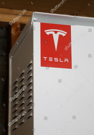 This April 20, 2015 photo shows a prototype Tesla battery system that powers the home of David Cunningham in Foster City, Calif. Cunnigham installed the battery late last year to pair with his solar panels as part of a pilot program run by the California Public Utilities Commission to test home battery performance. Tesla is expected to unveil a stationary battery for homeowners and businesses on