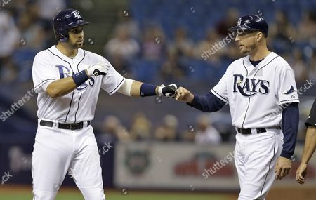 Tampa Bay Rays' James Loney, left, high fives first base coach Rocco Baldelli after his RBI single scores Steven Souza Jr. off New York Yankees starting pitcher Chase Whitley during the first inning of a baseball game, in St. Petersburg, Fla