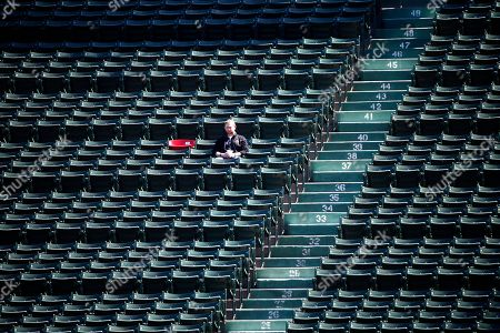 A fan sits next to the red seat which marks the spot of an historic home run by former Red Sox's Ted Williams before a baseball game against the New York Yankees in Boston