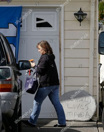 """A woman walks past a cement sign that reads """"the world loves Amanda,"""", at the home of Edda Mellas, the mother of Amanda Knox, in Seattle. Judges on Italy's top criminal court were deliberating Friday whether to overturn the murder conviction of Knox and her ex-boyfriend in the 2007 slaying of Knox's roommate"""