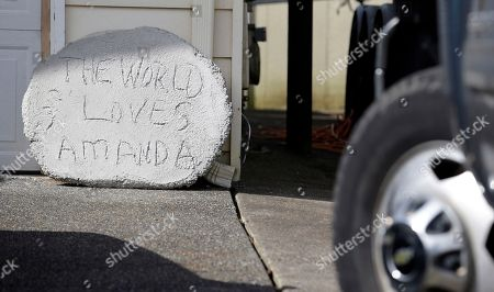 """A concrete stepping stone reading """"the world loves Amanda,"""" leans on a garage, at the home of Edda Mellas, the mother of Amanda Knox, in Seattle. Judges on Italy's top criminal court were deliberating Friday whether to overturn the murder conviction of Knox and her ex-boyfriend in the 2007 slaying of Knox's roommate"""