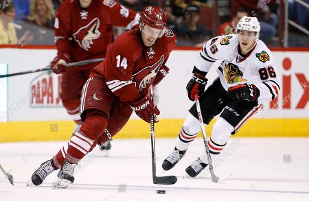 Joe Vitale, Teuvo Teravainen Arizona Coyotes' Joe Vitale (14) skates with the puck as Chicago Blackhawks' Teuvo Teravainen (86), of Finland, skates behind during the second period of an NHL hockey game, in Glendale, Ariz. The Blackhawks defeated the Coyotes 2-1