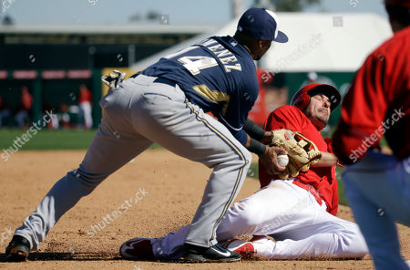 Milwaukee Brewers' Luis Jimenez tags out Los Angeles Angels' Matt Joyce at third as he tried to advance from first on a hit during the fourth inning of a spring training baseball game, in Tempe, Ariz