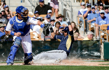 Milwaukee Brewers' Luis Jimenez, right, scores on a double by Hunter Morris as Los Angeles Dodgers catcher A.J. Ellis waits for the throw during fifth inning of a spring training baseball game in Glendale, Ariz., on