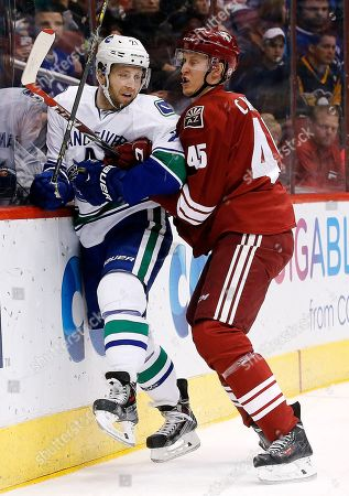 Brandon McMillan, Andrew Campbell Arizona Coyotes' Andrew Campbell (45) checks Vancouver Canucks' Brandon McMillan (21) into the boards during the first period of an NHL hockey game, in Glendale, Ariz