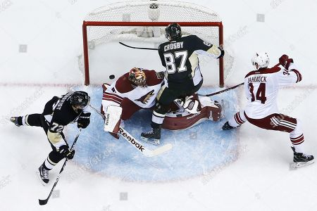 Sidney Crosby, Mike Smith, Joe Vitale Pittsburgh Penguins' Sidney Crosby (87) puts the puck behind Arizona Coyotes goalie Mike Smith (41) and Klas Dahlbeck (34) to score a goal during the third period of an NHL hockey game in Pittsburgh, . The Penguins won 3-2 with Crosby's goal being the game-winner