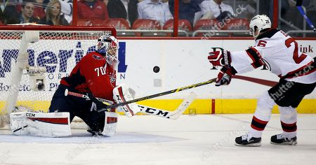 Braden Holtby, Patrik Elias Washington Capitals goalie Braden Holtby (70) knocks the puck away as New Jersey Devils left wing Patrik Elias (26), from the Czech Republic, reaches for it, in the third period of an NHL hockey game, in Washington. The Capitals won 3-2 in overtime