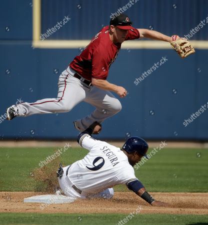 Milwaukee Brewers' Jean Segura is forced out at second by Arizona Diamondbacks second baseman Aaron Hill after Luis Jimenez hit into a double play during the third inning of a spring training baseball exhibition game in Phoenix, on