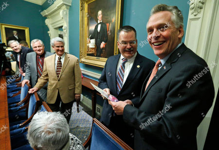 Terry McAuliffe, Edward Scott Virginia Gov. Terry McAuliffe, right, accepts a joke gift from Del. Edward Scot, R-Madison, second from right, as he talks with members of the House and Senate adjournment committee at the Capitol in Richmond, Va., . The 2015 session of the Virginia General Assembly adjourned after agreement on an ethics bill