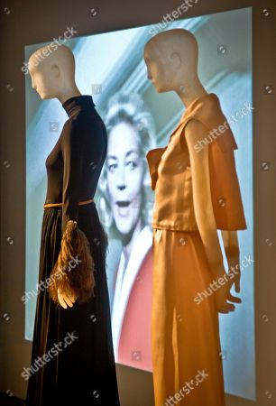 """Lauren Bacall This photo shows a video projection of the late actress Lauren Bacall flanked by mannequins wearing her designer garments, Christian Dior, left, and Norman Norell during a preview of the exhibition """"Lauren Bacall: The Look,"""" in New York. The evening gowns are part of a four-team Fashion Institute of Technology (FIT) graduate student exhibition, exploring Bacall's career and personal style, running through April 4 at The Museum at FIT"""